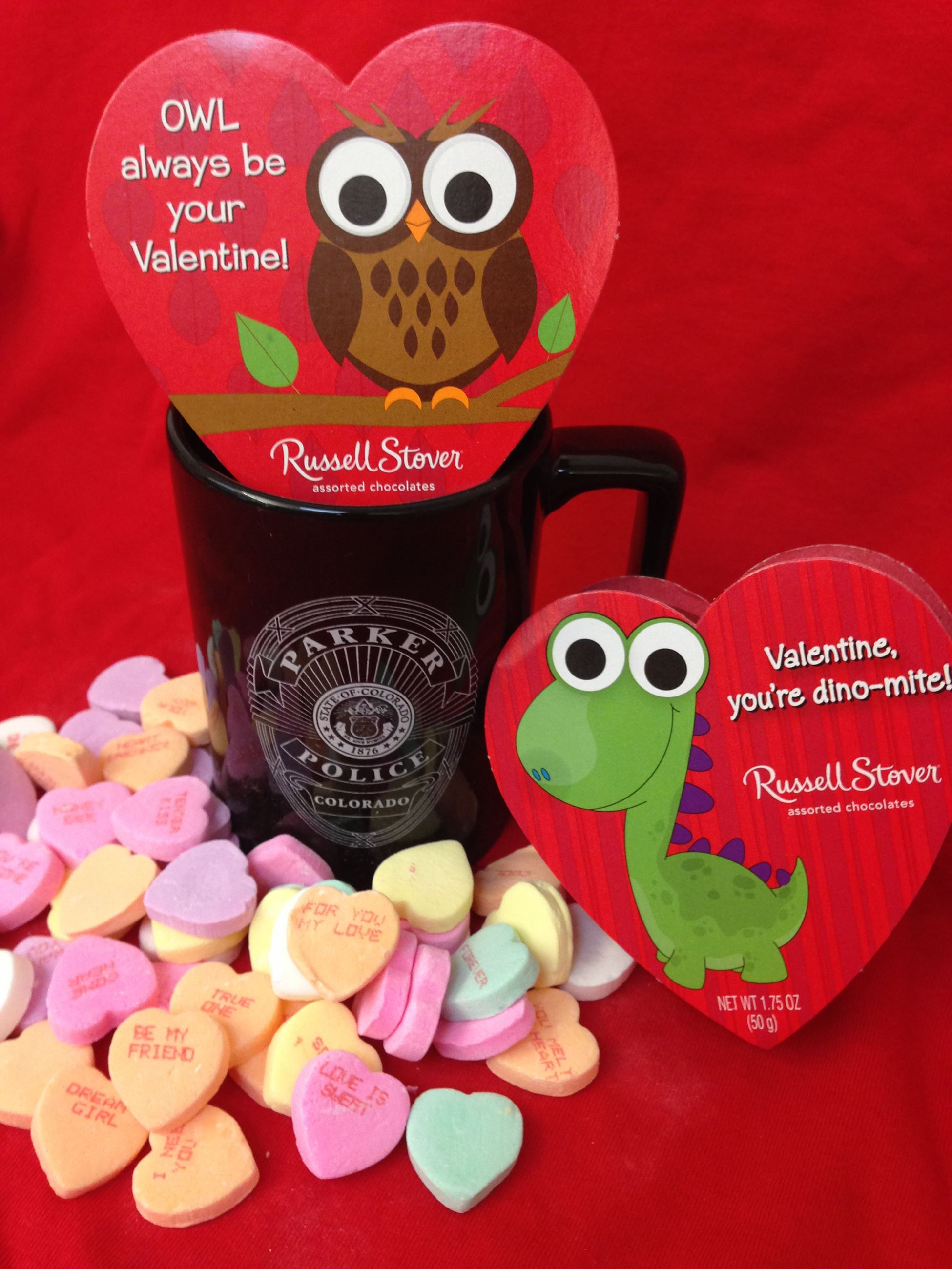 A Parker police department cup surrounded by candy hearts and two small boxes of candy