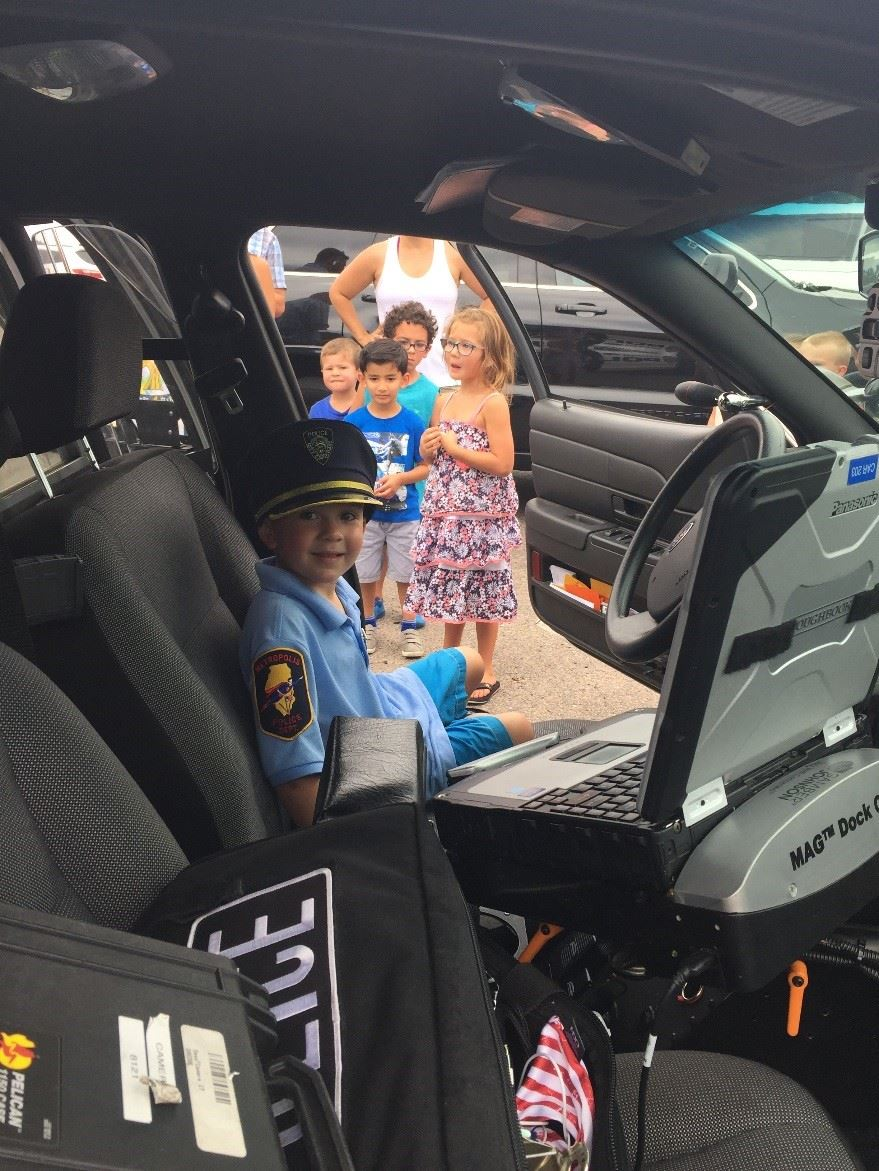 young boy sitting in a patrol car wearing a police hat